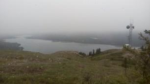 Die Berge im Hintergrund des Sees werden von grauen Wolken verschluckt. Wer genau hinsieht, erkennt auf der Wiese und auf den Bergen weisse Punkte. Das sind keine Pollen, sondern ziemlich kalte Schneeflocken, die der Wind ueber uns hinwegpeitscht.