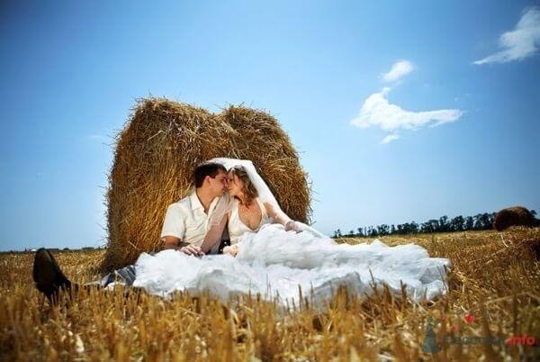 Молодожены целуются у стога сена.