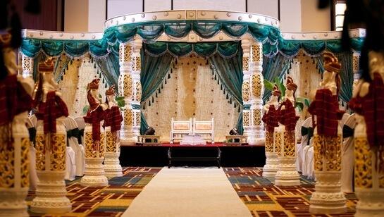 Банкетный зал.На индийской свадьбе жених и невеста сидят на помосте, на отдельных креслах, похожих на трон.