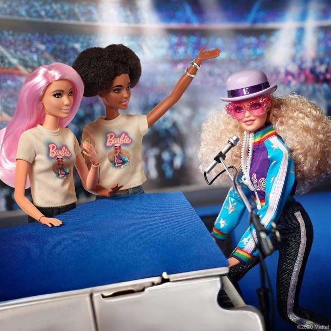 Barbie Elton John: imagem da boneca ao piano, tocando, com duas bonecas ao lado assistindo, uma branca de cabelos rosa e a outra negra de maria chiquinha. Ambas vestem uma camiseta com a imagem da boneca principal.
