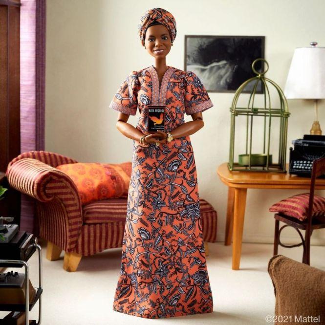Barbie Maya Angelou: foto de corpo inteiro da boneca, que veste vestido e turbante alaranjados com a mesma estampa, de pé em uma sala em miniatura de aparência confortável.