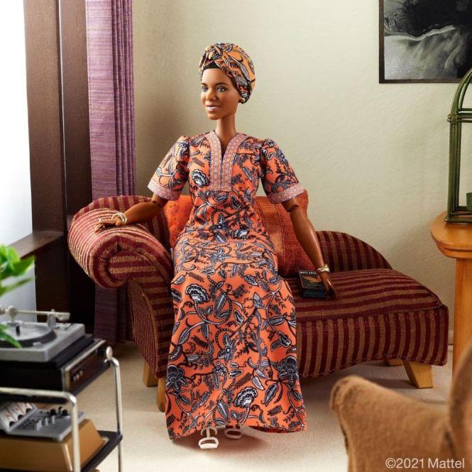 Barbie Maya Angelou: foto de corpo inteiro da boneca, que veste vestido e turbante alaranjados com a mesma estampa, sentada em uma sala em miniatura de aparência confortável.