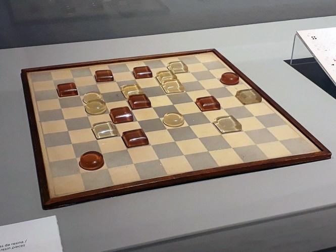Objeto lúdico criado pelo artista, representando um jogo de damas com tabuleiro simples e peças em resina em dois tons diferentes, representando times, e formatos circulares e quadrados dentro dessas cores.