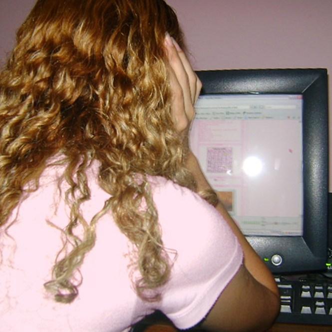 O resgate de memória: foto de Luly Lage aos 17 anos, de costas, de forma onde só é possível ver os cabelos loiros e cacheados e um pedaço da blusa clara. Ela está apoiada na mão direita olhando para a tela do computador, que exibe em primeiro plano o blog Sweet Luly com o visual que tinha na época.
