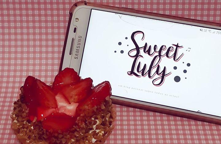 Foto de uma superfícia quadriculada de rosa claro e branco onde há um doce de morango e um celular com a tela ligada na página principal do blog Sweet Luly.