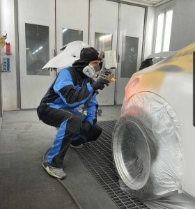 man in luma iii premium spray suit spray painting SEMA car