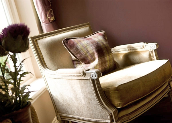 Taupe chenille chair with plaid cushion in purples - Interior Design Advice for Hotels
