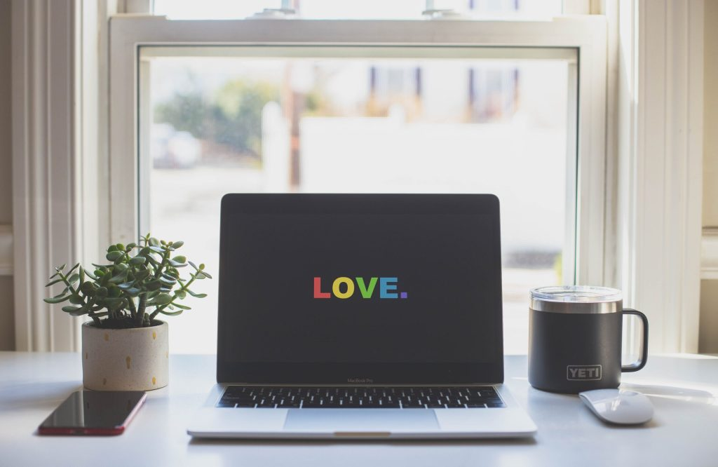 computer with love spelled out in rainbow letters
