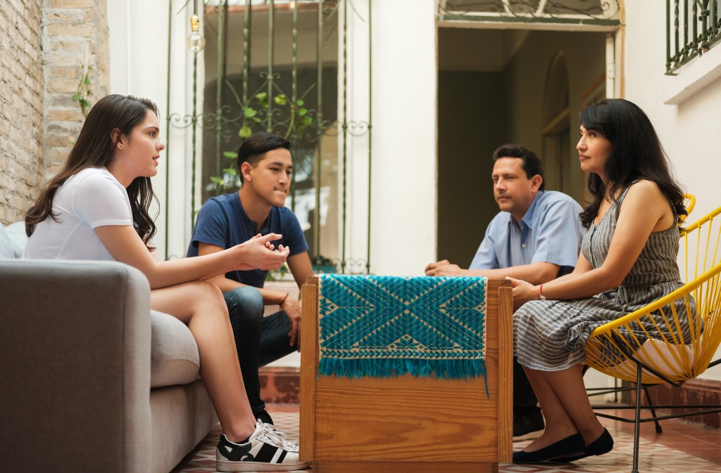 Family sitting around a coffee table discuss a life-limiting diagnosis