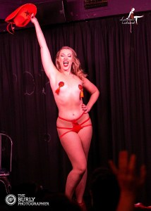 Bella Rose posing with one arm in the air holding a cowboy and hat.  One hand on hip, wearing red pants and red nipple tassels