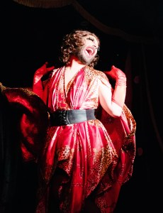 Drag Queen posing gleefully on stage