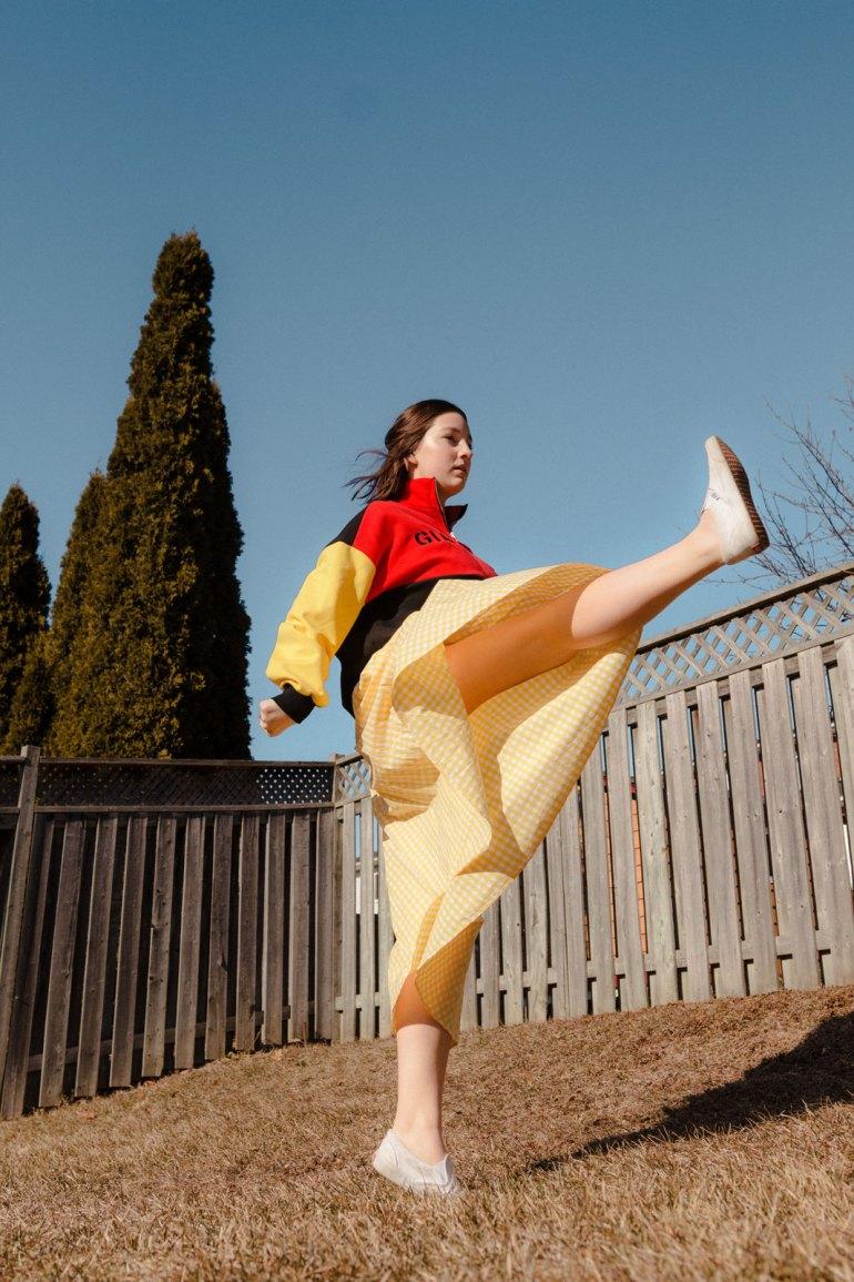 Emily Gilmore—Girl in yellow dress kicking in backyard
