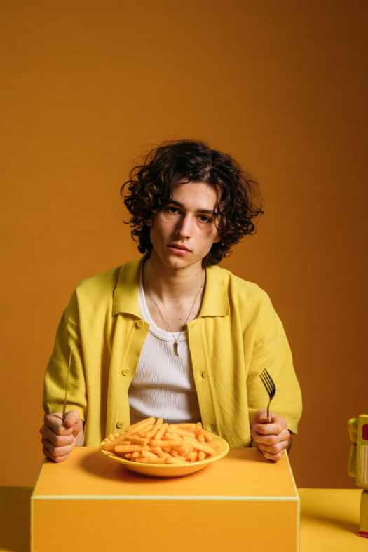 young man with a sad face sitting by the table with food