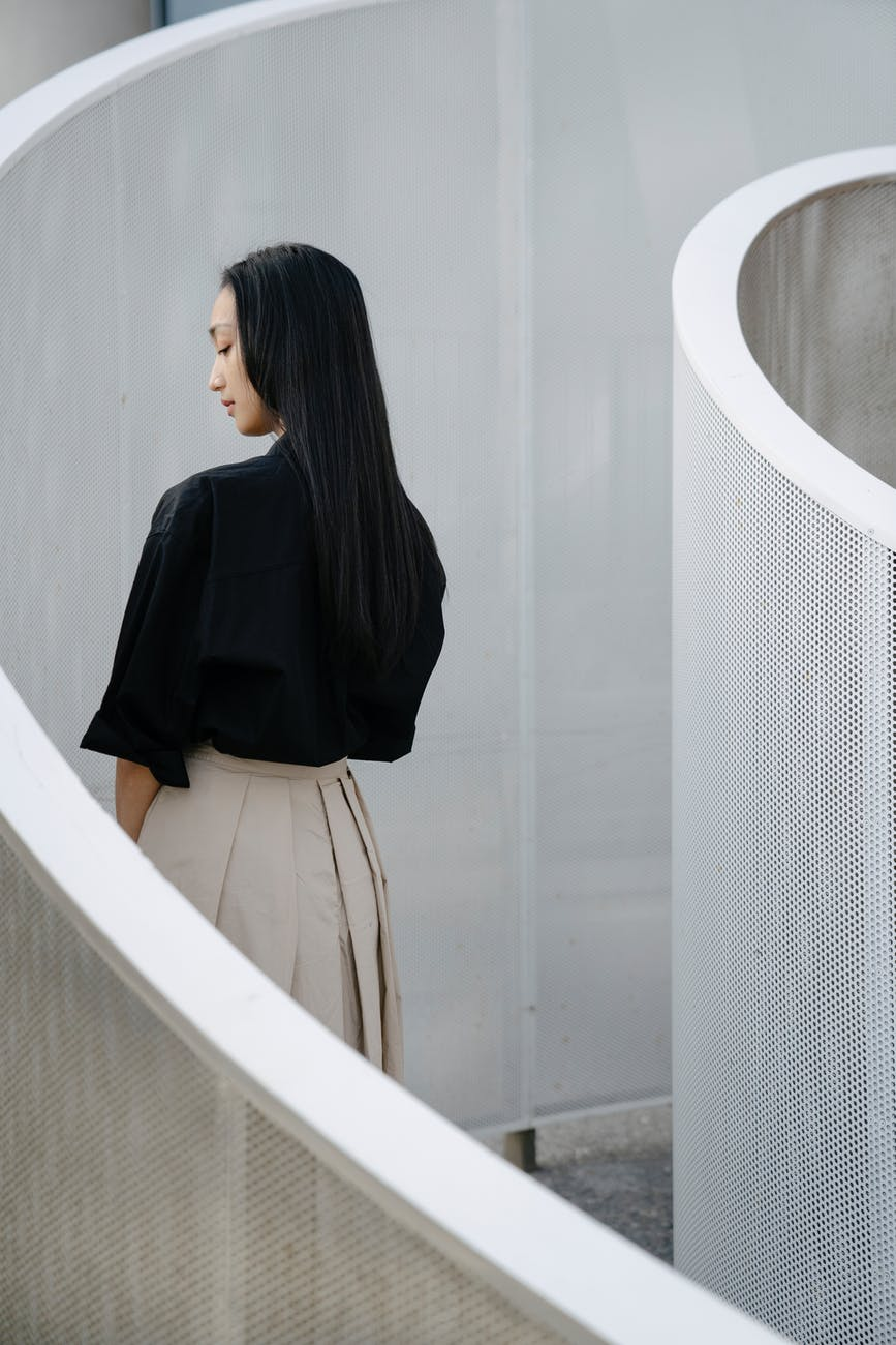 pensive young ethnic woman standing in curvy passage on street