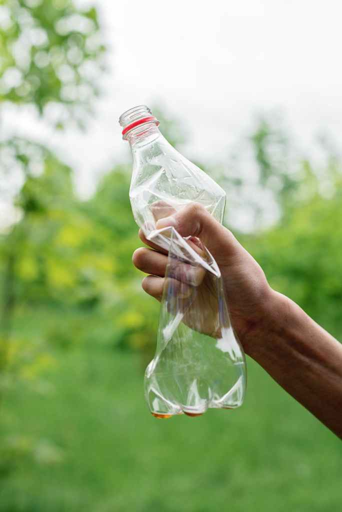 person holding a crumpled plastic bottle