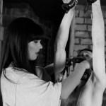 dominatrix put a gag on a hanged slave