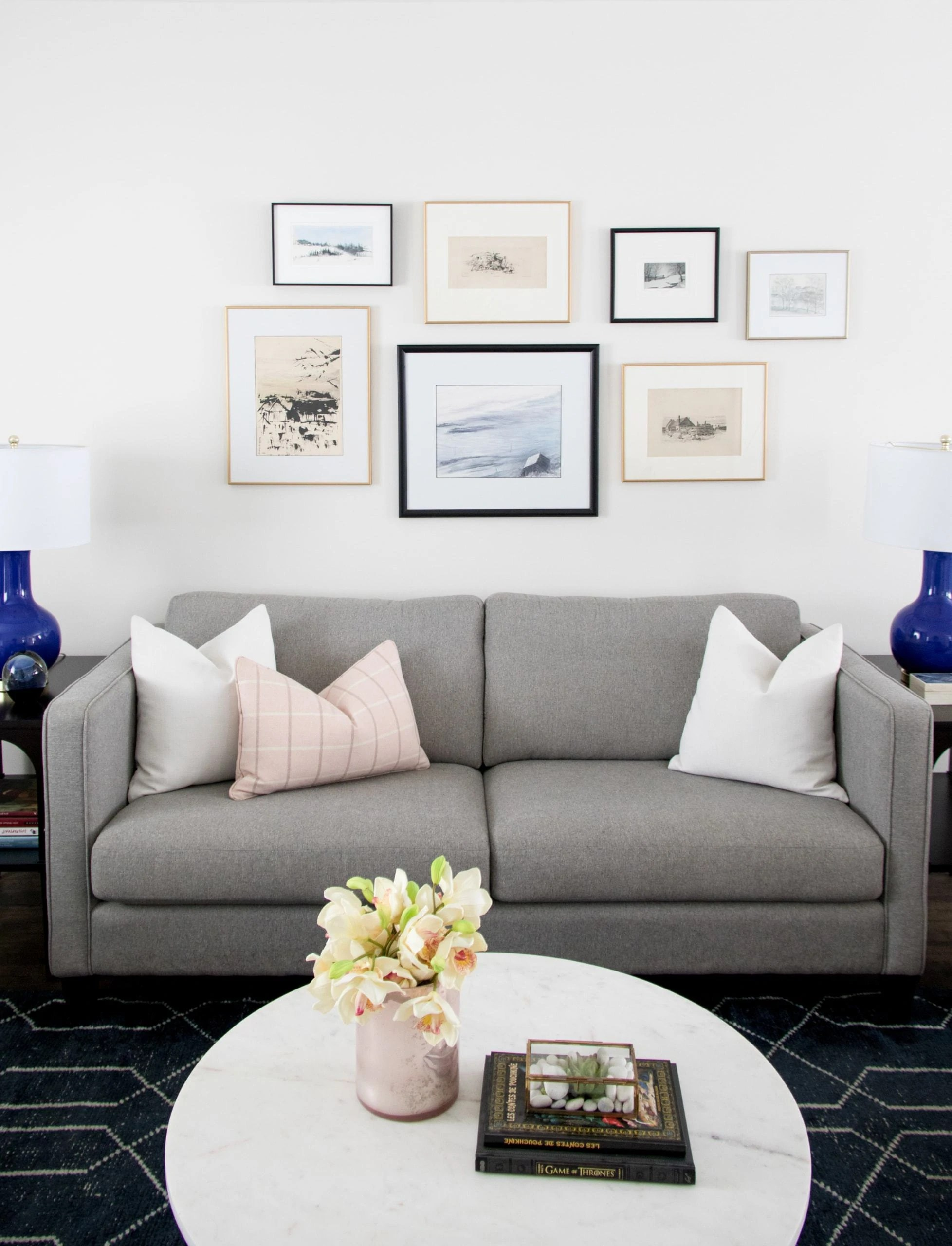 Gray couch with pictures above it inside a living room