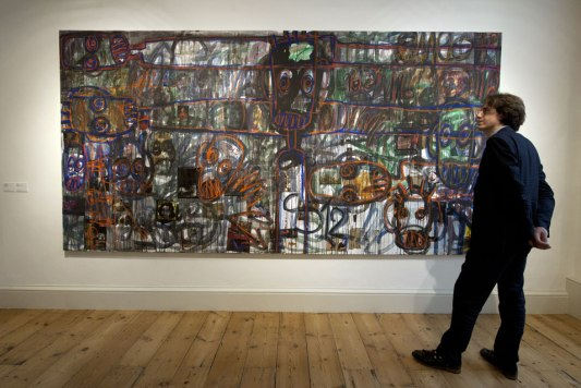 A visitor looks at a painting by Ivorian artist Aboudia displayed at the Contemporary African Arts Fair at Somerset House in Central London