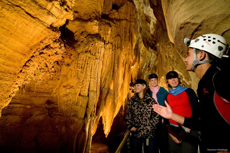 Guides explain the natural history that has lead to exquisite limestone formations in the Waitomo Caves. Courtesy of Tourism Holdings