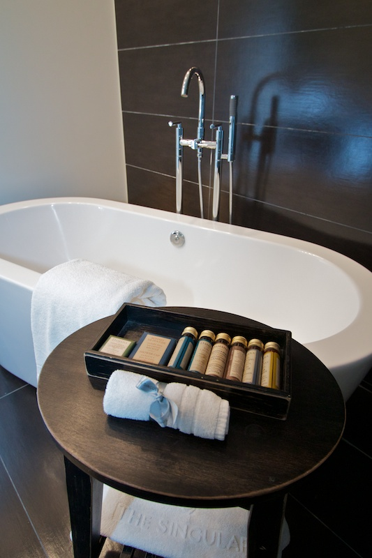In the bathroom, a tub that can easily accommodate two sits next to the glass walk-in shower