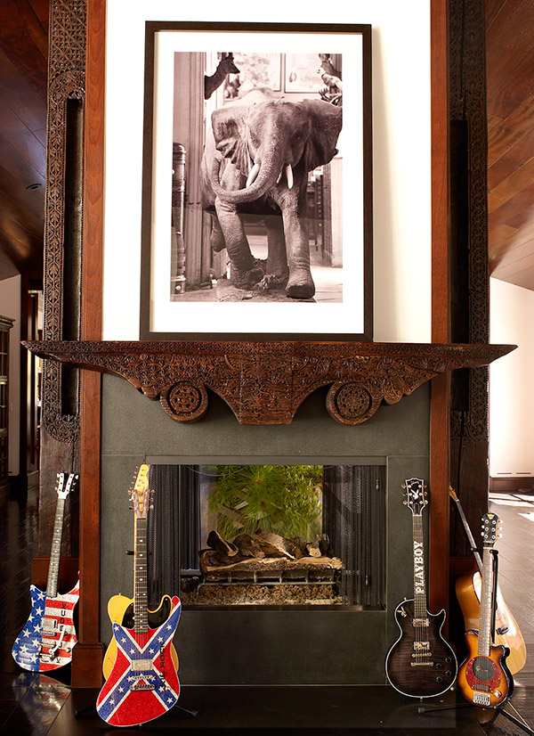 Kid Rock's black soap stone fireplace surrounded by his collection of guitars.