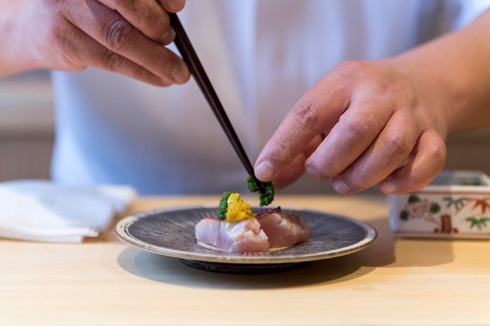 Sushi Shin Chef Plating a Kinmedai Appetizer in Annupuri Village Niseko on LuxNiseko Alpine Luxury Lifestyle Magazine
