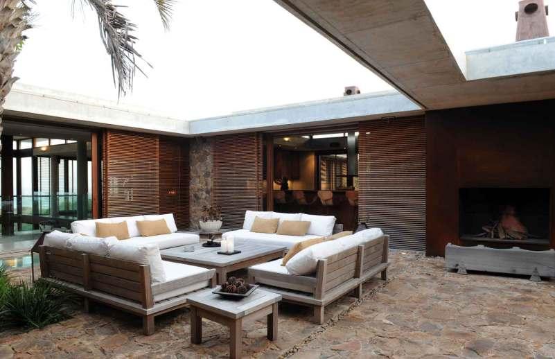 Udendørsområde. Lokalt piedra de campo-stengulv, specialfremstillet sofa og bord i lapachotræ med puder fra Sunbrella samt lanterner fra en lokal smed.