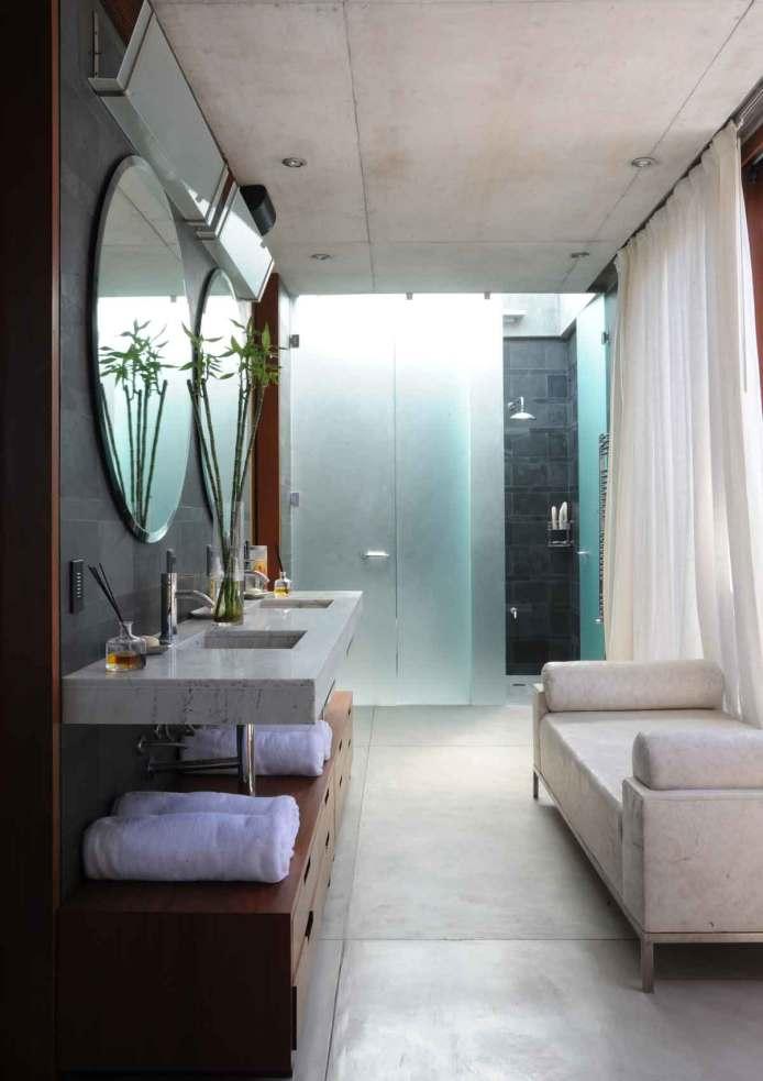 Soveværelse og tilhørende badeværelse. Specialfremstillede skabe i lapachotræ, lokal sort vægflise i skifer, gulv med varme i afpudset beton og bordplade i marmor fremstillet af sten fra lokalt brud.
