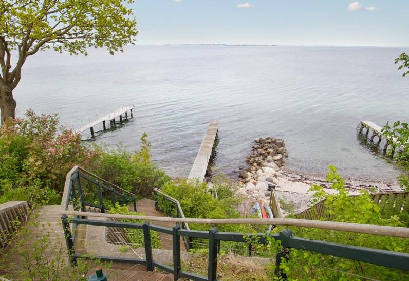 Der hører privat strand med solterrasser og badebro til palæet, der er sat til salg for 29,5 mio. kr.