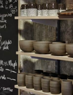 På hylderne i Trines Fournais' hyggelige butik ser man mange forskellige designs. Hun foretrækker, at man kan se materialet, og at keramikken er håndlavet.