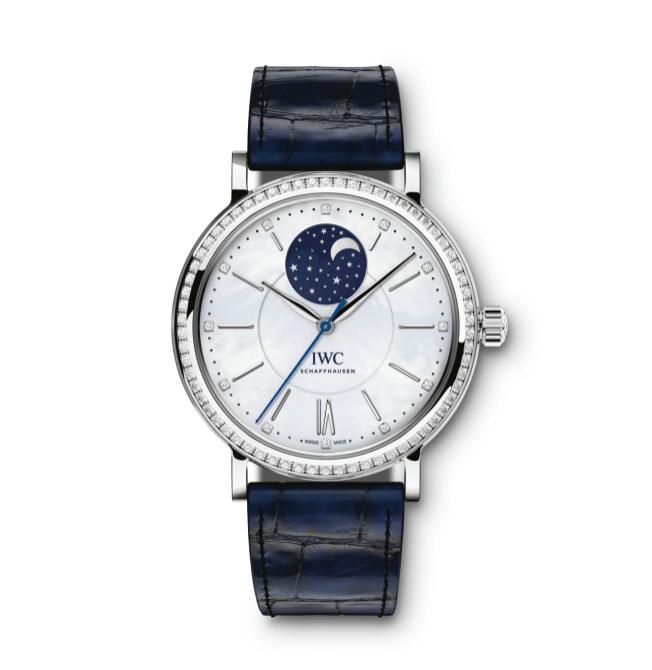 Yndigt, klassisk og feminint ur i rustfrit stål beklædt med 66 diamanter, hvid perlemorsskive med 12 diamanter og en blå Santoni-rem i krokodilleskind. IWC Portofino Automatic Moon Phase, 103.000 kr.