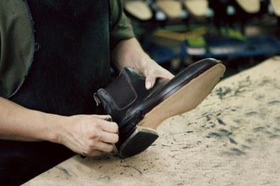 Farven på kanten af sålen påføres med håndkraft for at få den rigtige finish.