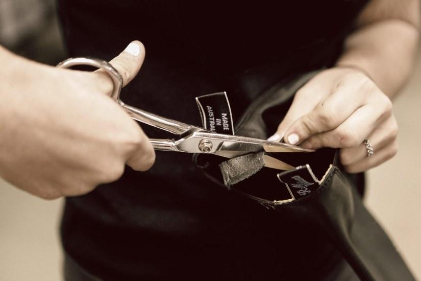 Læderet trimmes med saks, efter at de velkendte stropper er syet i.