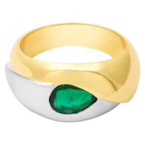 Swirl of 18k yellow and white gold ring featuring a 0.60 cts deep green emerald