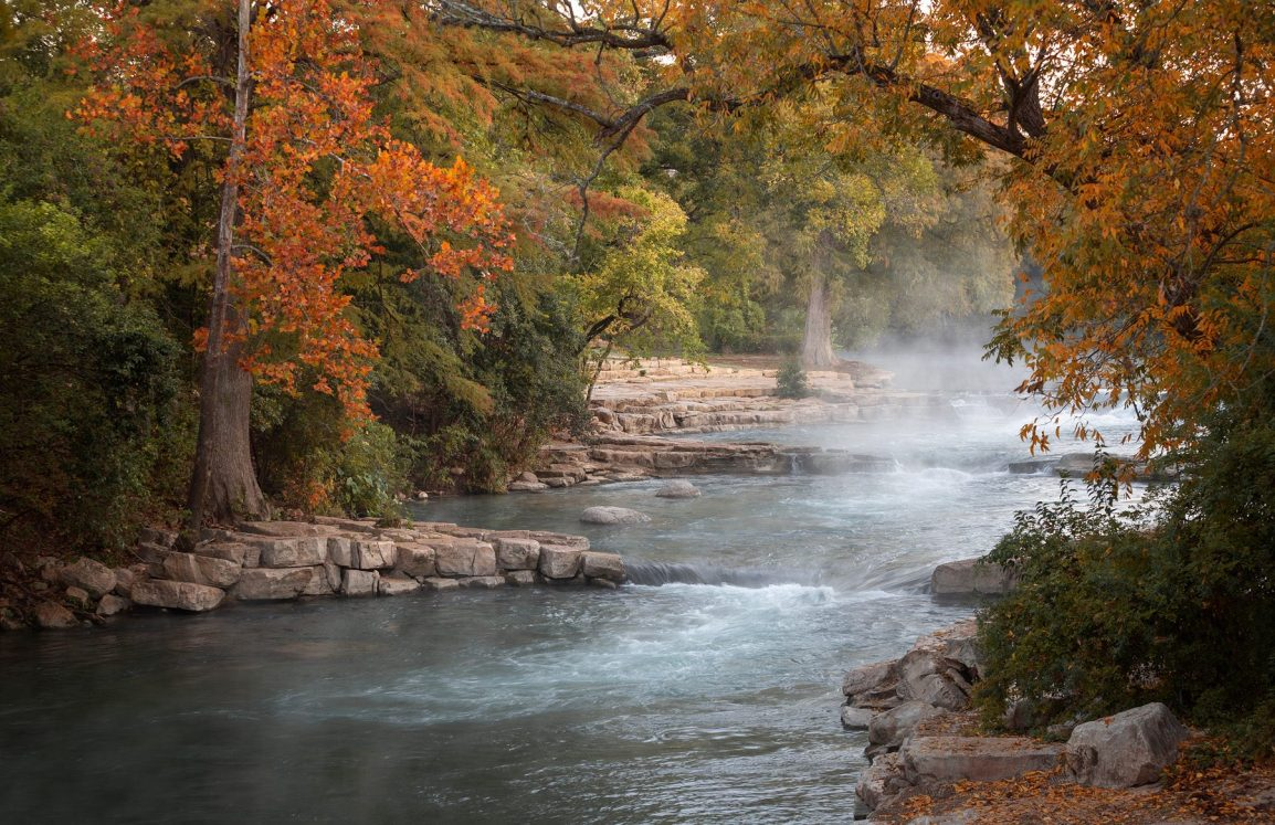 Steaming river view at Rio Vista Park with surrounding rock landscaping at trees during the Fall.