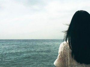 Pay God is like diving into a deep ocean. Girl overlooking ocean expanse.