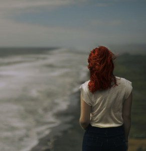 Redhead woman walking by ocean meditating on Greatest Overcomer