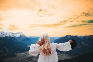 Young lady balancing near mountain and beautiful sky view.