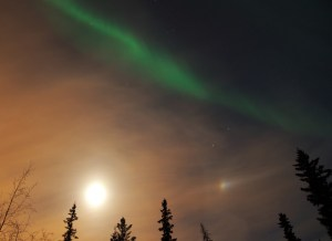 the aurora shining over the moon and a moon dog