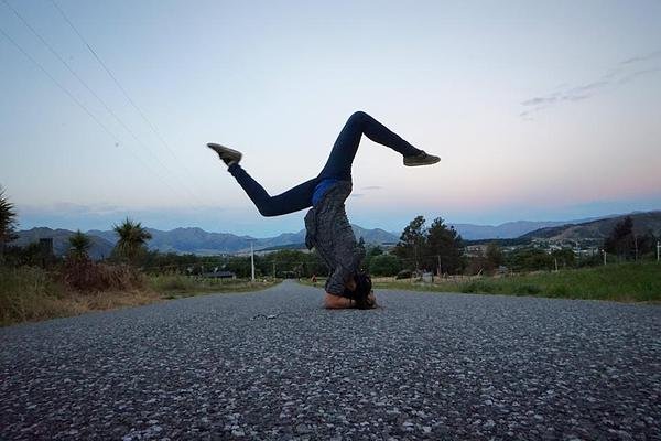 Yoga headstand pose in the middle of the road