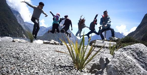 Group jumpshots with the view of Milford Sound.