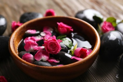 Spa composition of stones and flowers in water, on wooden background