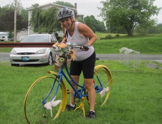 Lynda qui rit sur un vélo décoratif jaune et bleu agrémenté de fleurs