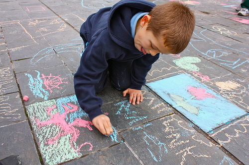 Image of a child drawing on the sidewalk