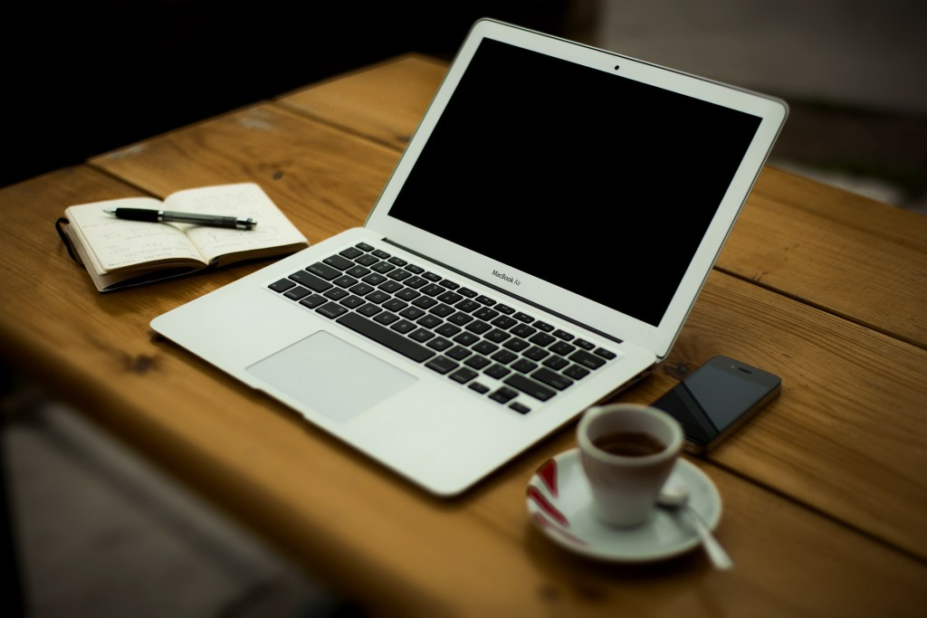 Image of a journal and pen lying on a wood table next to a laptop computer, a smart phone, and a cup of coffee-definitely one set of writing resources.
