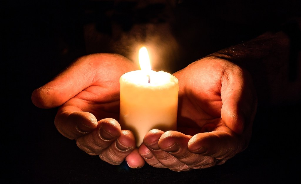 Image of hands cupped together & holding a lit candle, one way to find your inner peace