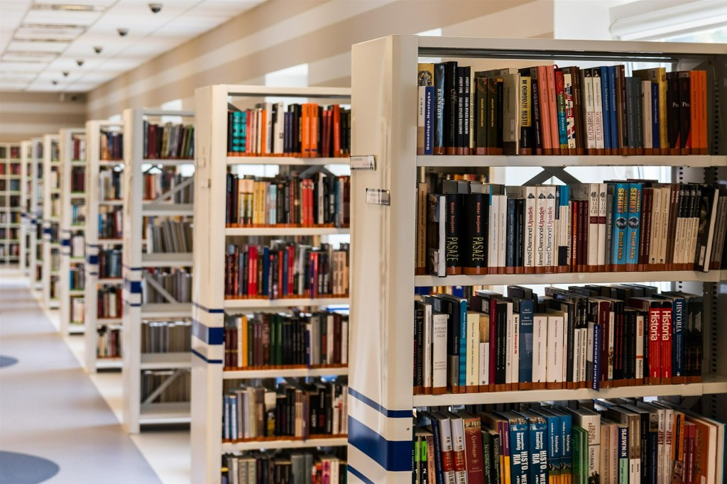 Photo of rows of bookshelves in a library, part of 41 Quotes about reading