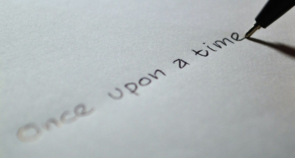 "Image of a pen writing ""Once upon a time"" on paper--Story Time Review a blog series by Lynette M. Burrows reviewing audio versions of short stories."