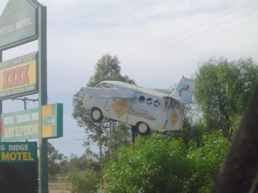"Photo of a ""flying van"" near a motel sign not exactly the Jetson life"