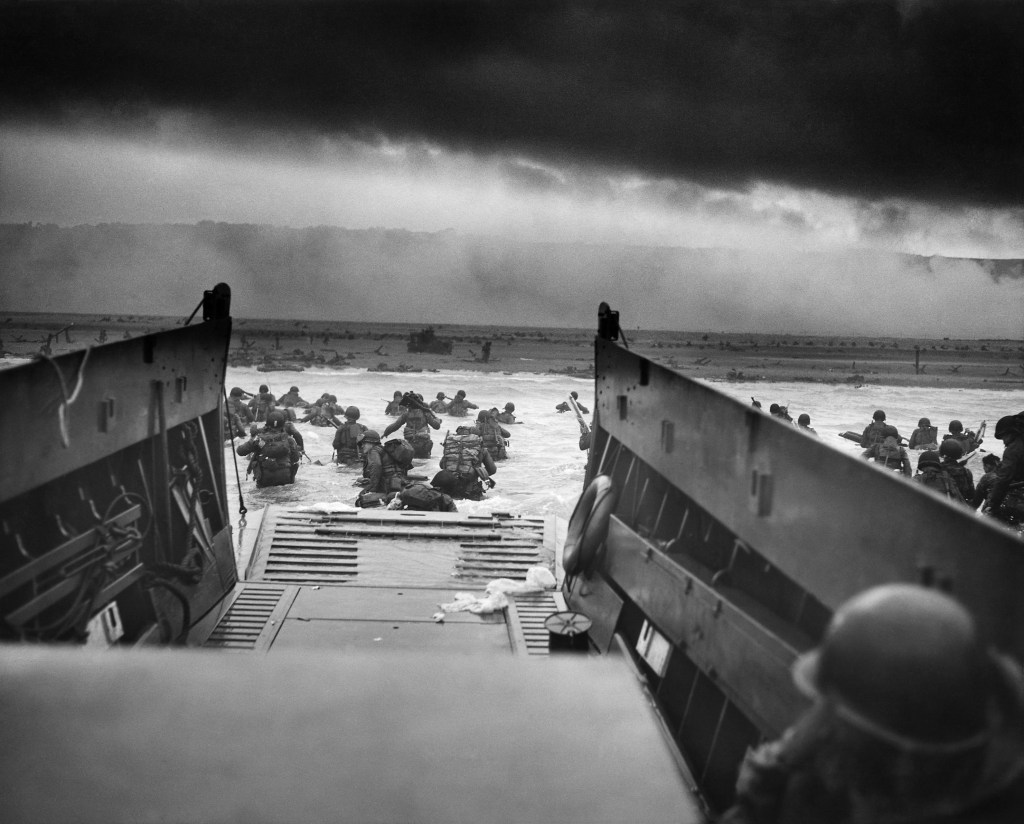 Photograph shot looking out of the boat with soldiers wading to the Normandy shore. A musical and literary tribute for D-Day